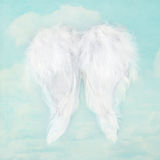 White angel wings on textured sky background. White angel wings on textured blue sky background Royalty Free Stock Image