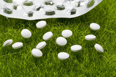 White antibiotic pills and empty blister pack scattered on the grass Stock Images