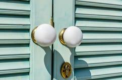 White antique door knob. Outdoor view. White antique door knob on wooden door and keyhole Stock Photos