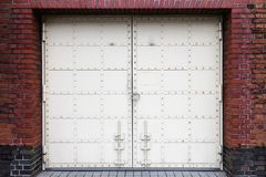White antique iron door with lock on red brick wall background a Stock Images