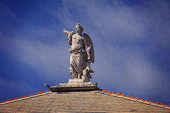 White antique statue decorating the top of a building in Genoa Royalty Free Stock Image