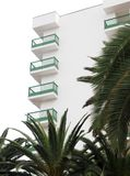 White apartment building with balconies behind green palm trees. And a bright sky in tenerife spain Royalty Free Stock Images