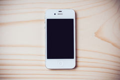 White Apple iPhone 4s. Odessa, Ukraine - January 21, 2015. White Apple iPhone 4s on wooden background. This smartphone was designed and developed by Apple Inc Stock Photos
