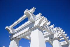 White arbor. Detail of white arbor against blue sky stock photo