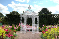 White arbour in a garden. Wrought iron arbour and bench in an English garden Royalty Free Stock Image