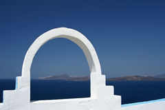 White arc. Gives a view to Thirassia and Nea Kameni - Santorini, Greece Royalty Free Stock Photos