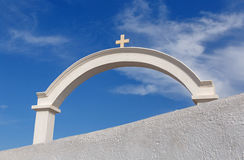 White arch with cross in Oia Stock Photography