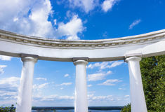 White arch with doric columns against blue sky. White arch with doric columns against river and blue sky Royalty Free Stock Photo
