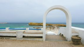 White arch and fence on beach with umbrellas and rocks near the sea. Waves on the sea at cloudy day stock footage