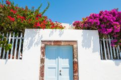 White architecture, blue door and pink flowers