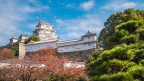 The white Architecture of Himeji Castle in autumn in Japan. Himeji Castle is a 17-th century Iconic castle known for a white facade, plus towers, surrounded by royalty free stock photography