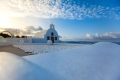 White architecture on Santorini island, Greece. Beautiful old white ortodox church in sunny day with blue sky in Oia on Santorini island. Santorini is romantic Royalty Free Stock Image