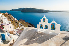 White architecture on Santorini island, Greece. Bell tower in Oia town. Beautiful view on the sea Stock Photography