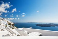 White architecture on Santorini island, Greece. Deck chairs on the terrace with sea view. White architecture on Santorini island, Greece Royalty Free Stock Images
