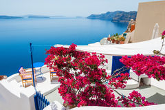 White architecture on Santorini island, Greece. Terrace with relax area and red flowers. White architecture on Santorini island, Greece. Beautiful landscape with Royalty Free Stock Photos