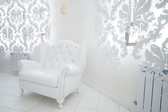 White armchair. Beautiful white armchair in a modern apartment Royalty Free Stock Photo
