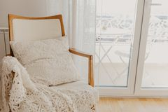 White armchair with plaid and pillow . Provence style royalty free stock image