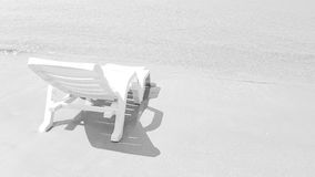 White armchair on the wet beach in sunny time Royalty Free Stock Photos