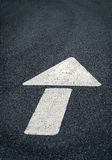 White arrow. Painted white traffic arrow on asphalt road with cracks Stock Photos