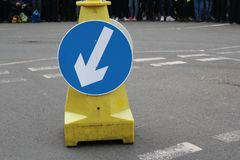 White arrow on blue traffic sign on road stock photos