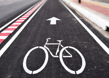 White arrow and bycicle sign on lanes road Royalty Free Stock Images