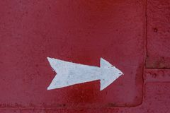 Arrow direction on deck. White arrow direction on red metal background on ship deck royalty free stock images