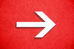 White arrow direction sign over vivid bright red color stucco rough wall as an empty rustic and simple background texture. With empty space stock photos