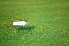 White arrow on green grass Stock Photos