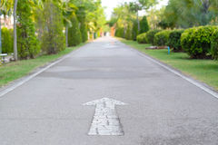 White arrow moving forward on the road. Running in public park royalty free stock photos