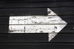 White arrow painted onto a black wooden shed wall Royalty Free Stock Photos