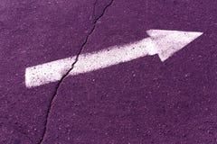 White arrow on purple asphalt surface. Royalty Free Stock Photos