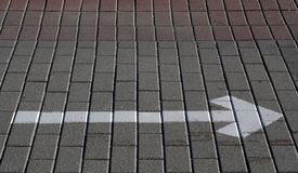 White arrow with right direction on the pavement. Signs and symbols stock photo