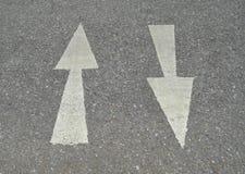 White arrow sign on asphalt road Stock Photos