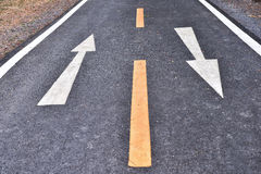 White arrow sign marking on road surface in the park Royalty Free Stock Images