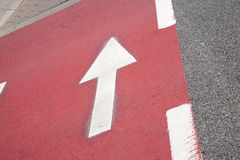 White Arrow Sign on Red Cycle Path Royalty Free Stock Image