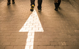 White arrow straight on pavement walking street with walking peo Royalty Free Stock Photo