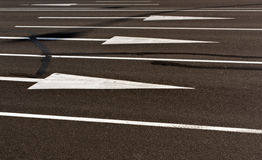 White arrows and lines on cracked asphalt surface. Stock Photos