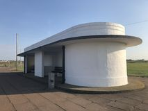 Art Deco shelter, New Brighton, Wirral. White Art Deco shelter, New Brighton, Wirral,  near a pavement, grass and under a blue sky Royalty Free Stock Photo