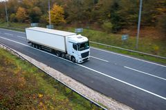 White articulated lorry on the road. White articulated lorry with box trailer in motion on the road stock photos