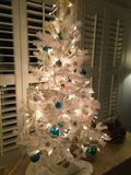 A White Artificial Christmas Tree with Ornaments. A pretty 4 foot Artificial white Christmas Tree with Gold and Silver and Teal blue colored ornaments. White stock images