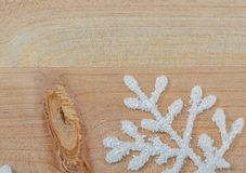White artificial snowflakes on a light wooden table. Christmas decoration background and copy space for text. Closeup. royalty free stock images