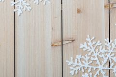 White artificial snowflakes on a light wooden table. Christmas and New year decoration background and copy space for text. Closeup royalty free stock image