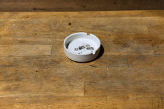 White ash tray on wooden table. Royalty Free Stock Image