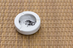 A white ashtray on wooden table. A white ashtray on wooden table, unhealthy concept background Royalty Free Stock Photo