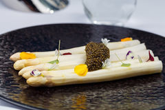 White asparagus served with caviar decorated with flowers on black plate. Royalty Free Stock Photo