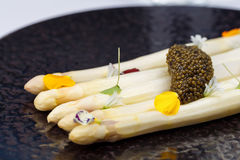 White asparagus served with caviar decorated with flowers on black plate. Stock Images
