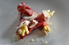 White asparagus wrapped in bresaola ham and decorated with hard Stock Photo