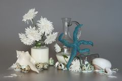 White aster flowers in a glass with milk, sea shells, quail eggs and starfish blue color, still life for an interior wall. White aster flowers in a glass with Royalty Free Stock Photography