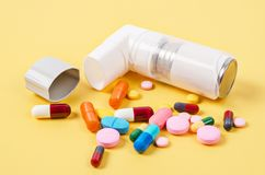 White asthma inhaler and colorful pills drug. Stock Photo