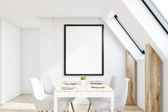 White attic kitchen. View of an attic kitchen with white walls, a long wooden table and a framed vertical poster. 3d rendering, mock up Stock Photography